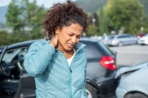 Woman Holding Neck in fear of whiplash from car accident