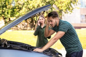 Texas Man and Woman in Front of Car Accident Vehicle Figuring out Filing a Claim